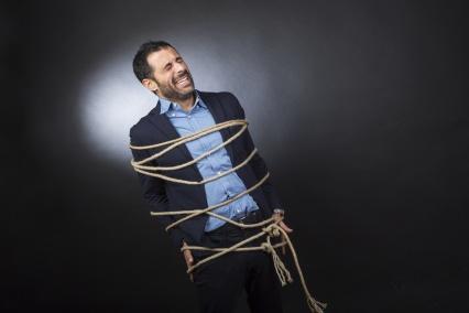 Uomo con giacca e camicia legato da un fune è disperato perché non può muoversi liberamente - sfondo nero